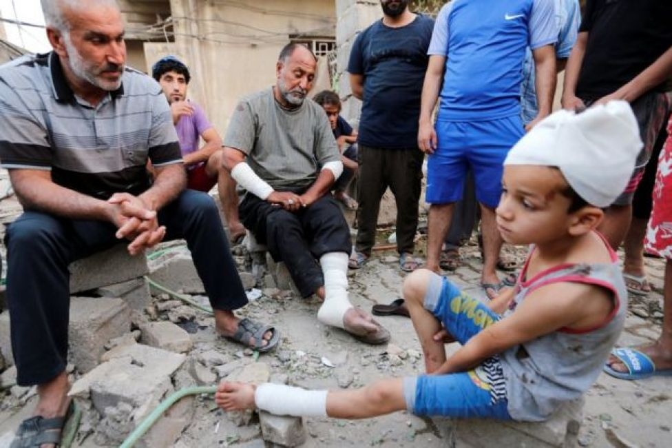 A man and his son, who were wounded by an explosion in Baghdad's Sadr City district (7 June 2018)