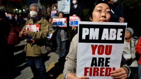 安倍首相の辞任を求める声が高まっている。写真の女性が掲げる紙には「安倍首相、あなたはくびだ!」と書かれている