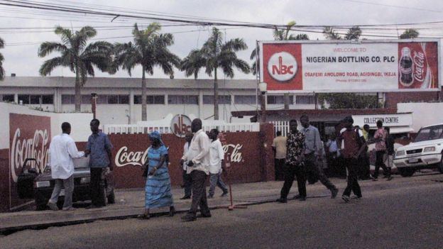 Passers-by walk past the Nigerian Bottling Company in Lagos