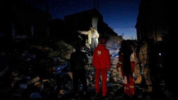 Bomberos sobre escombros