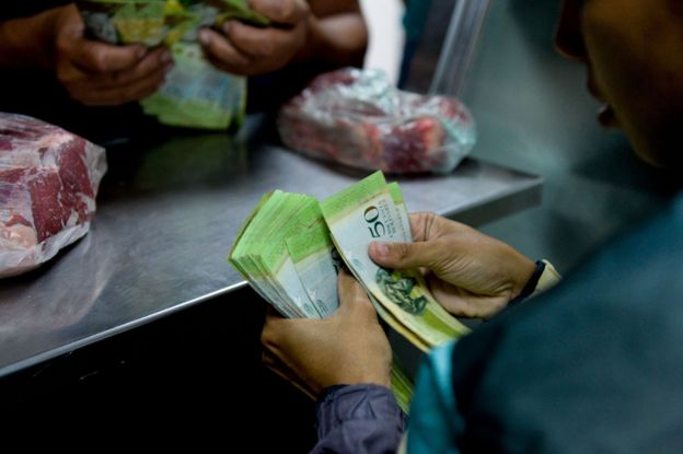 Shopper zahlt für Fleisch mit Garbe von Banknoten