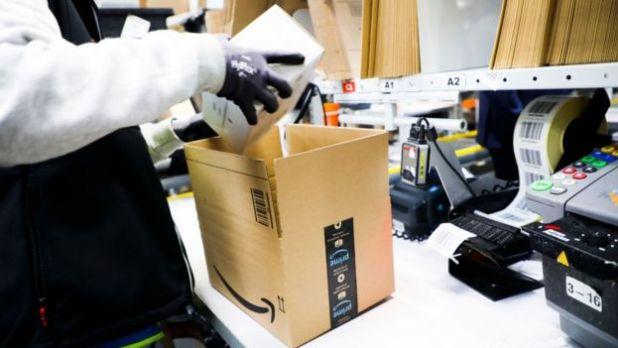 Eldiven giyen, bir kutuya öğeleri ambalaj Amazon işçi