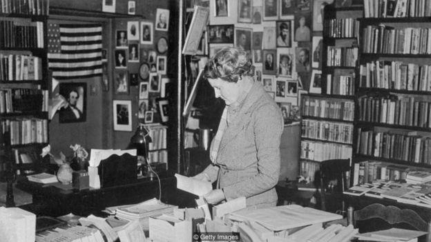 Pendiri Shakespeare and Co, Sylvia Beach, dipotret ketika sedang asyik membaca buku di dalam tokonya.
