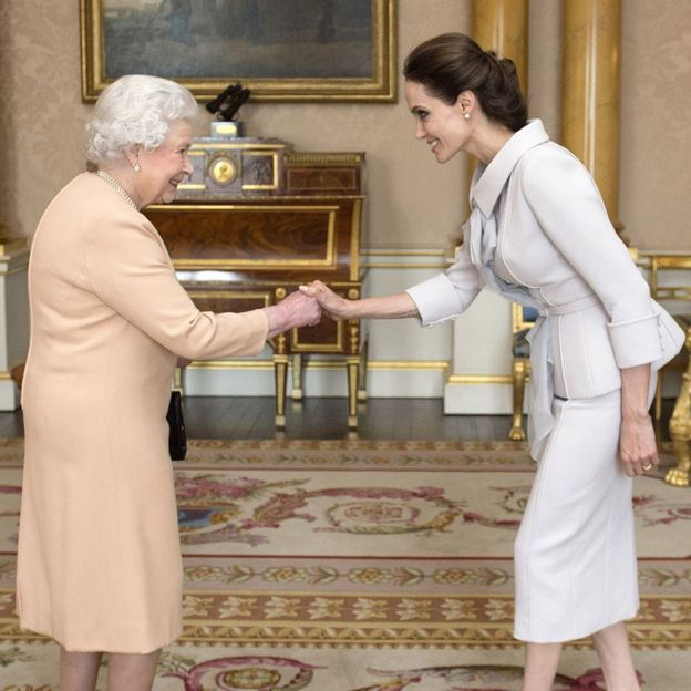 Actress Angelina Jolie (right) being presented with the Insignia of an Honorary Dame Commander of the Most Distinguished Order of St Michael and St George by Queen Elizabeth II