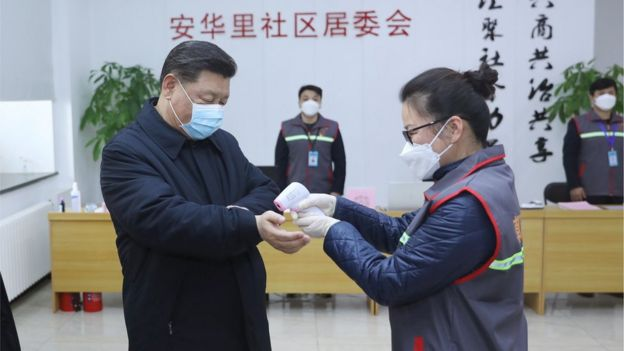 Chinese president Xi Jinping has his temperature recorded during a trip to a hospital in Beijing
