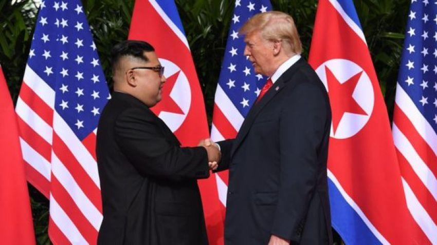 Mr Trump and Mr Kim shake hands