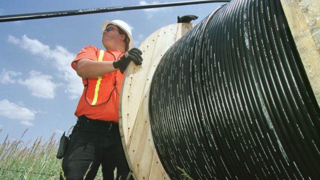 Trabalhador com rolo de fibra ótica.