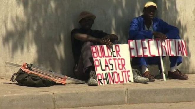 Men in South African touting for work holding the signs