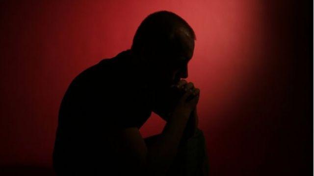 Foto da sombra de um homem em frente a uma luz vermelha