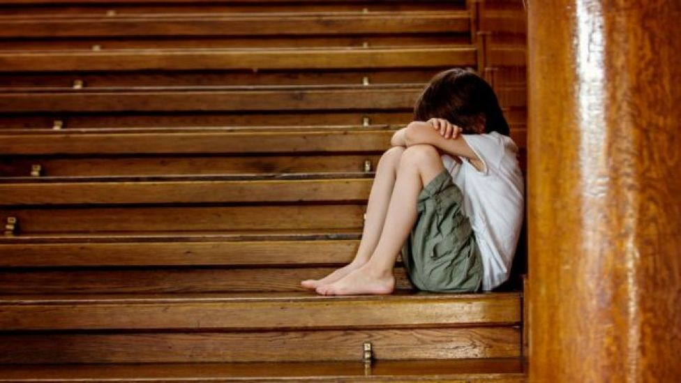 Niño con la cara tapada sentado en una escalera