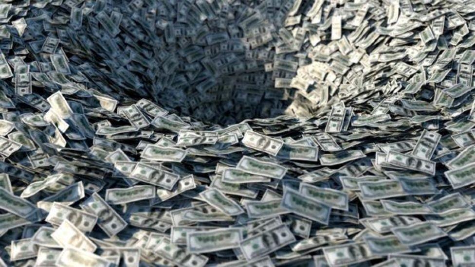 Dinero desapareciendo por un agujero.