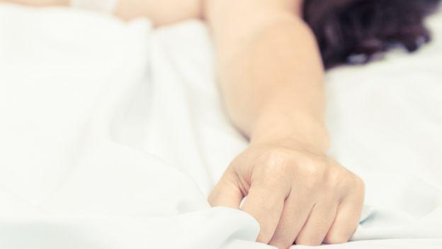 Mano de una mujer sujetando una sábana durante un orgasmo