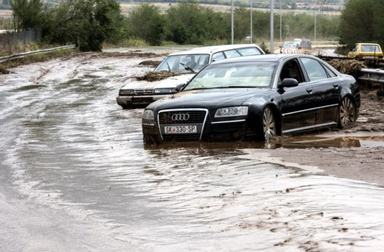 cars stuck in the mud next to flooded ring road