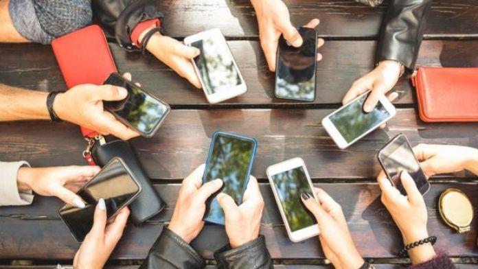 varias personas agarrando su celular.
