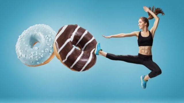 Mujer en constituye pateando 2 donuts gigantes.