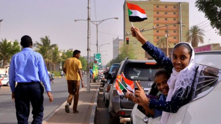Demonstrators wave flags after Sudan's defence minister said that President Omar al-Bashir had been detained in Khartoum, Sudan April 11, 2019