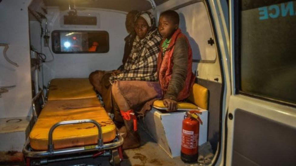 Local residents wait inside an ambulance after the Patel Dam burst