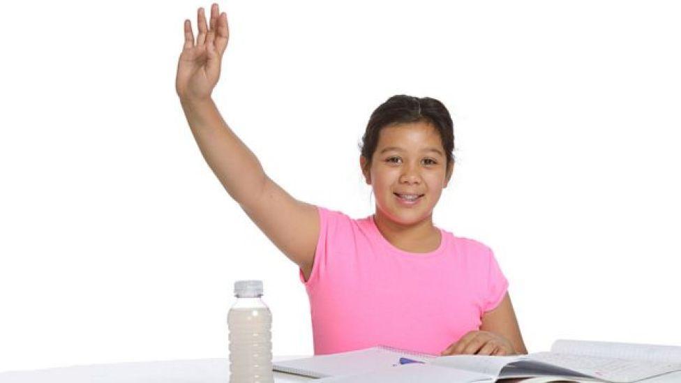Niña levantando la mano
