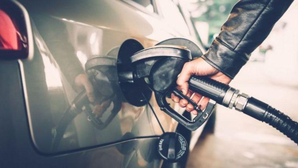Mujer recargando gasolina en un carro