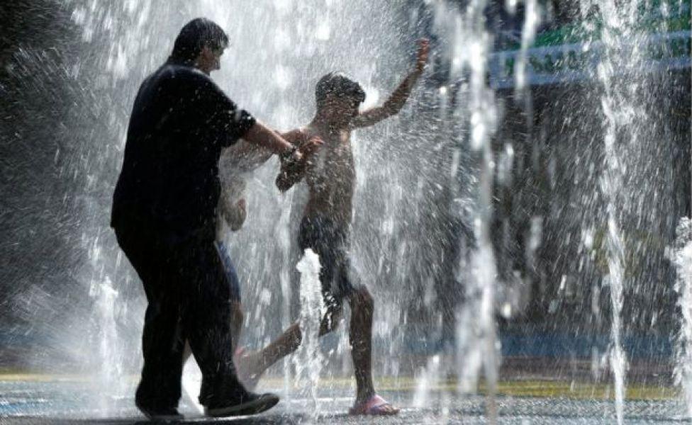 Las personas se refrescan en una fuente en Tbilisi.