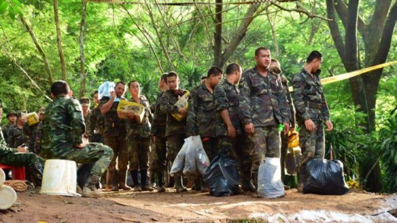 Soldados com suprimentos em área próxima à caverna