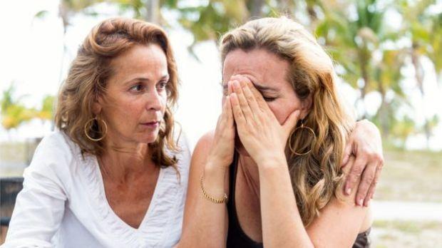 Uma mulher sendo confortada por outra