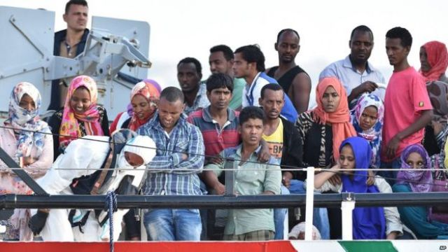 Migrants wait to disembark from the Italian Coast Guard ship Fiorillo in the harbour of Pozzallo, near Ragusa, Sicily, Italy (7 August 2015)
