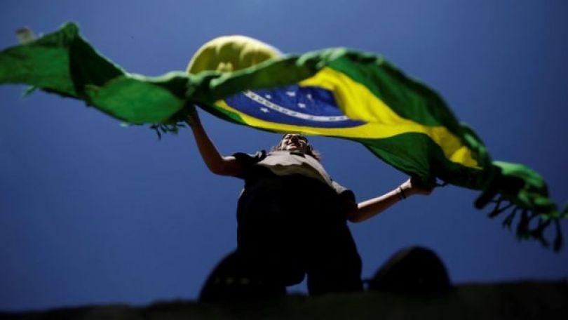 Mulher segura bandeira do Brasil