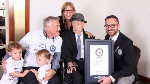 Marco Frigatti, of Guinness World Records, presenting Yisrael Kristal with his certificate of achievement for oldest living man, in the presence of the Kristal's daughter, her son and grandchildren.