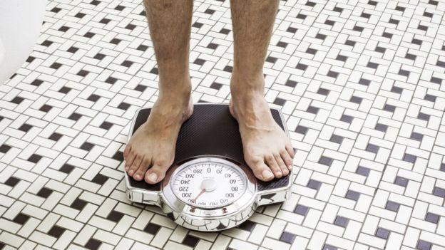Persona pesándose.