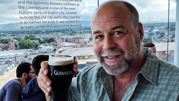 Steve Becker holding up a pint of Guinness beer