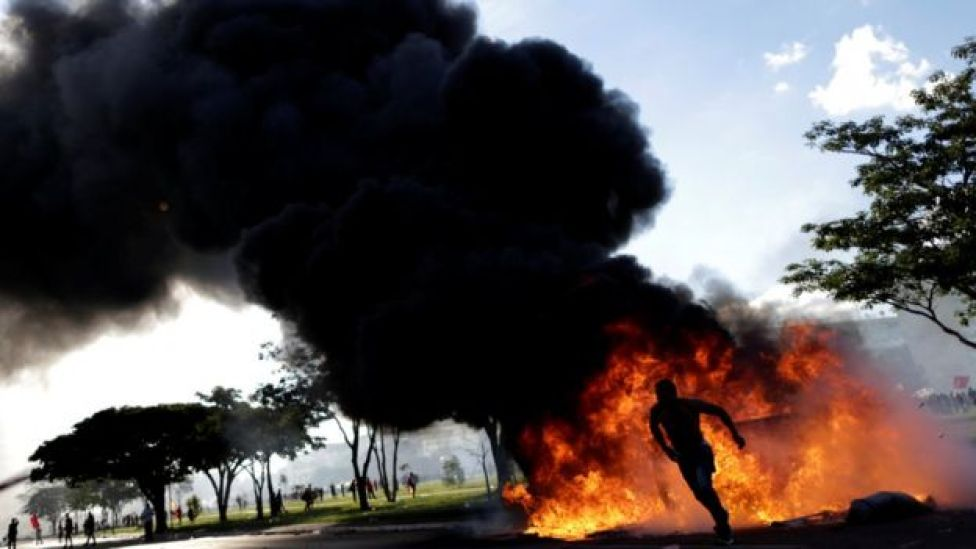 A demonstrator runs near a burning barricade during a protest against President Michel Temer in Brasilia, Brazil, May 24, 2017