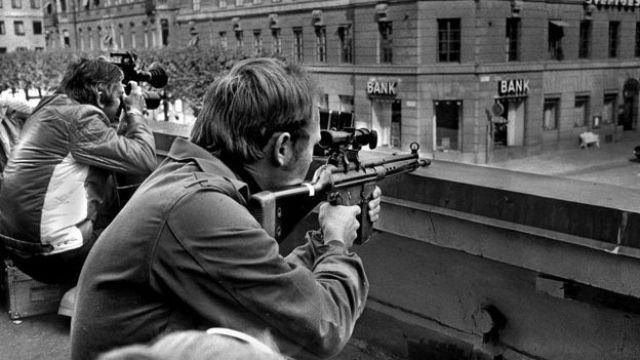Policía armado y periodista con cámara