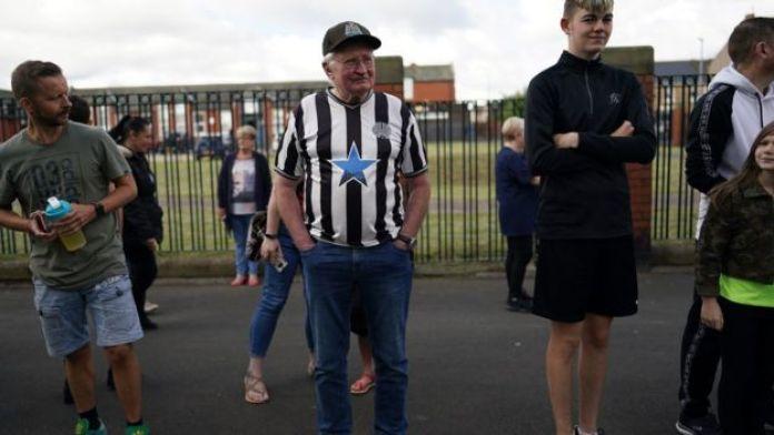 An elderly man in Ashington wears an old Newcastle United shirt and cap