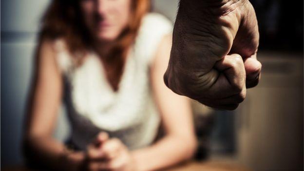 Mujer frente a puño de hombre