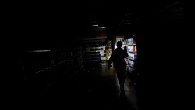 El trabajador de un supermercado inspecciona los daños causados a una tienda saqueada en Caracas.