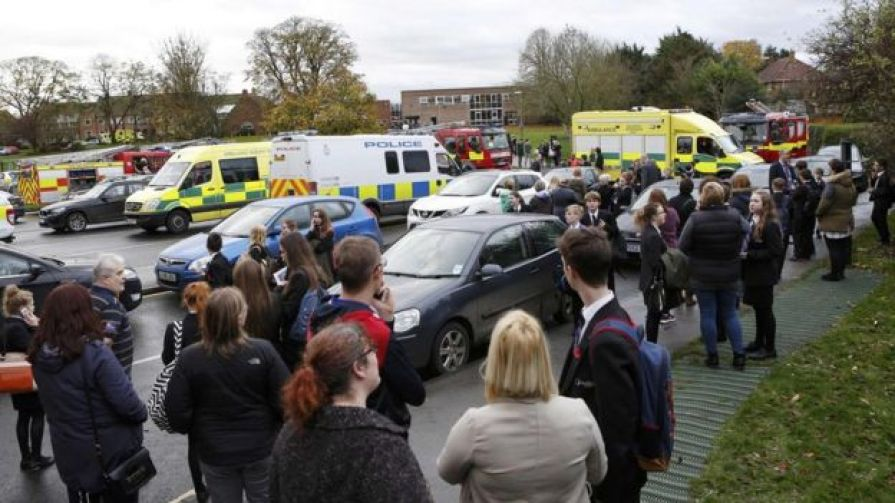 Pupils and staff stand outside Outwood Academy as emergency services attend to an incident at the school