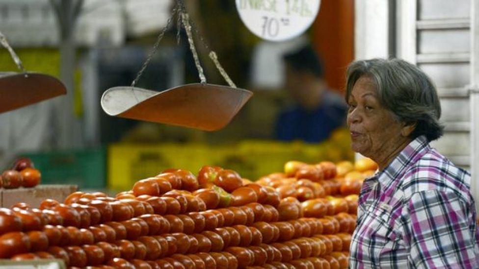 Una señora ante un puesto de tomates.