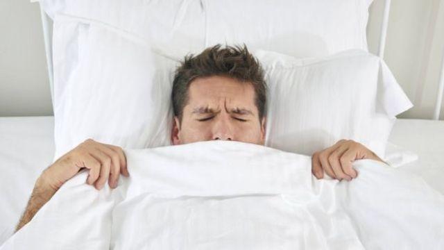 Hombre en la cama tapado en el edredón.