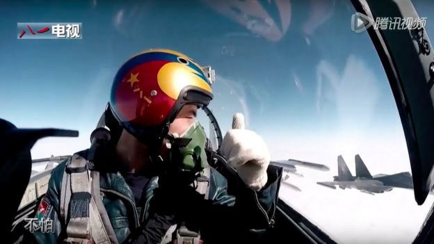 A pilot gives the thumbs-up to another plane, from the inside of his fighter jet's cockpit