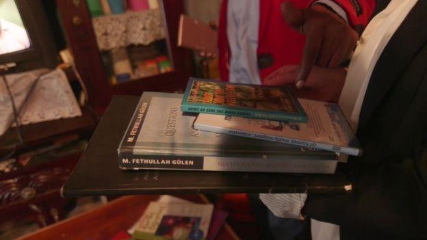 Huruma'da eski bir öğretmen, kendisine verilen Fethullah Gülen ve Said-i Nursi kitaplarını gösteriyor.