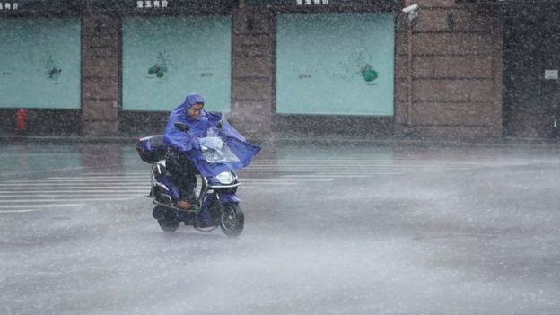 A man rides an electric scooter in the rainstorm as typhoon Lekima approaches in Shanghai, China