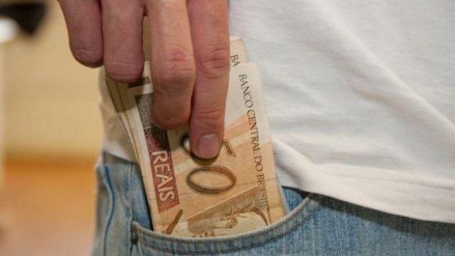 Pessoa colocando dinheiro no bolso