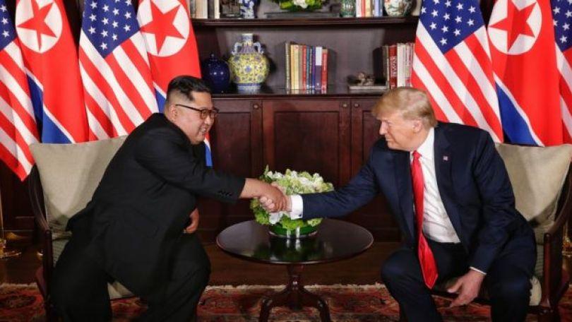 Kim Jong-un e Donald Trump apertam as mãos em frente a bandeiras da Coreia do Norte e dos Estados Unidos