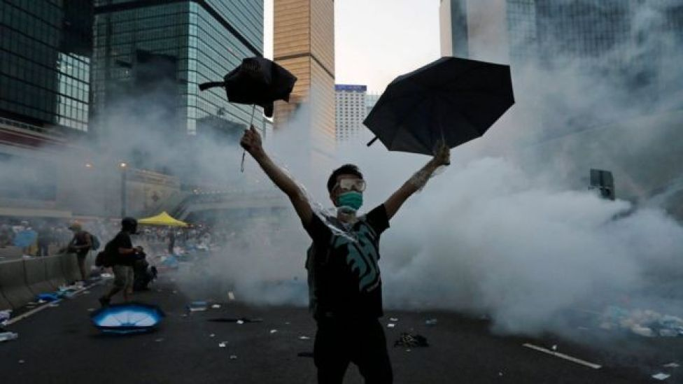 A protester (C) raises his umbrellas in front of tear gas which was fired by riot police to disperse protesters blocking the main street to the financial Central district outside the government headquarters in Hong Kong, September 28, 2014.