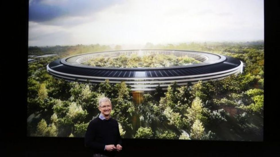 Apple boss Tim Cook in front of a rendering of the company's campus