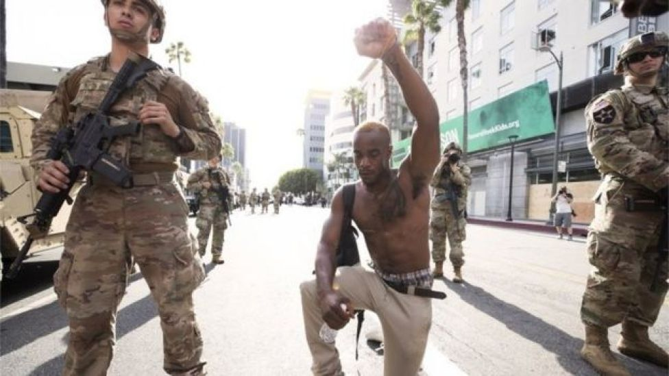 A demonstrator kneels during a march in response to George Floyd's death on June 2, 2020 in Los Angeles, California
