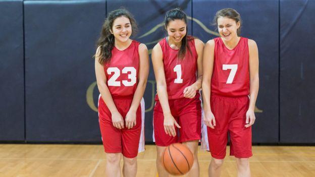 Tres adolescentes miembros del mismo equipo de baloncesto.