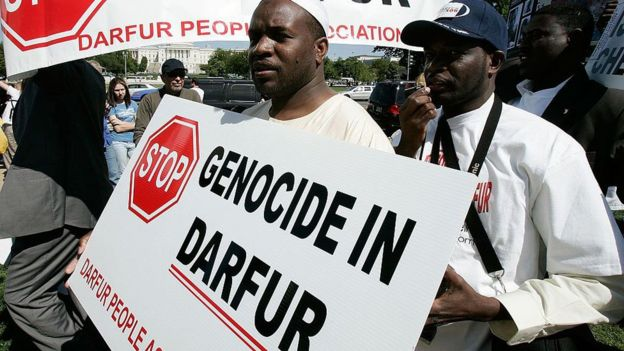 """Man holding a sign saying """"Stop genocide in Darfur"""""""