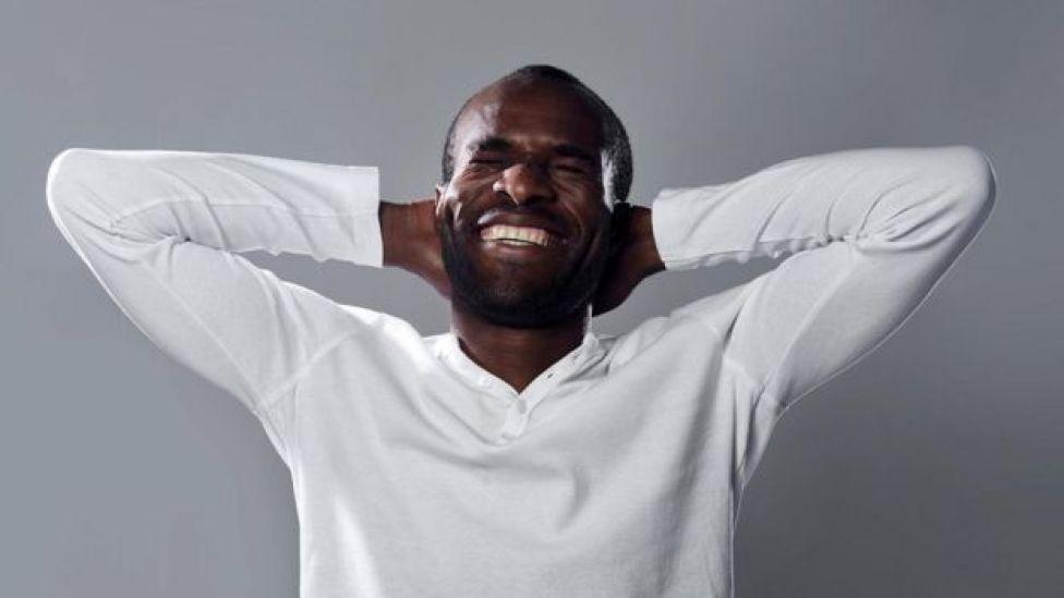 Hombre joven y sonriente de raza negra.